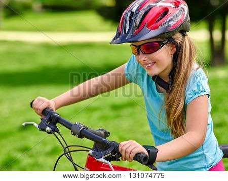 Bikes bicycling kid girl. Girl rides bicycle on green grass in park outdoor. Girl in cycling. Girl clings to bicycle handlebars.