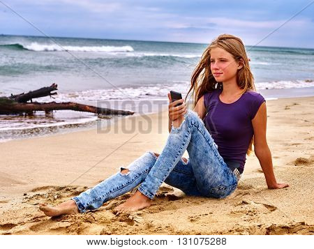 Teenager on sand near sea call help by phone. Snag in the background. Summer girl sea back on water.