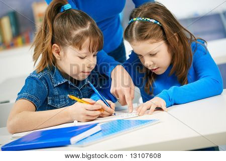 Schoolgirls learning together in primary school classroom. Elementary age children.?