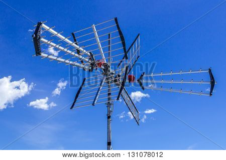 Directional antenna for reception of digital television broadcasting DVB-T and DVB-T2 against a blue sky. poster