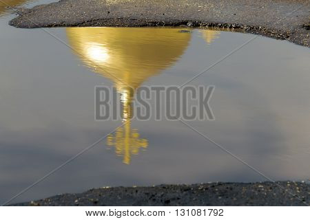 The yellow (gold) dome of the Church with the cross is reflected in a puddles of bad roads