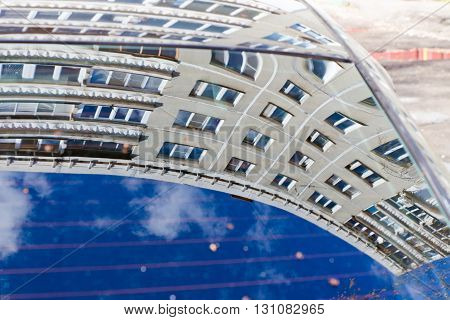 Multi-storey contemporary house reflected in the window of the car