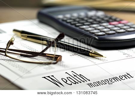 Wealth management. Calculator glasses and black pen on financial documents in the background.