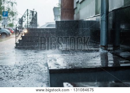 Rain water flowing from a metal downspout during a heavy rain. concept of protection against heavy rains.