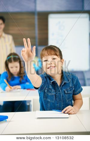 Schoolgirl raising hand to answer question smiling, other girl and teacher in background of class.?