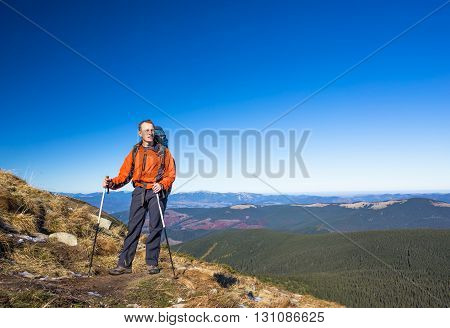 Young happy traveler hiking in beautiful mountains. Fantastic autumn landscape.