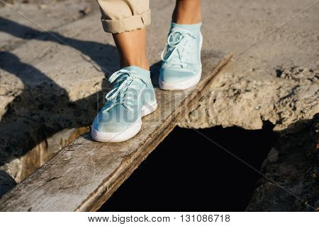 Female Feet In Beige Pants And Sneakers Are On The Board Over The Precipice