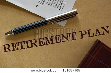 Pen rests on top of a vintage retirement plan certificate. A warm color scheme dominates the image.