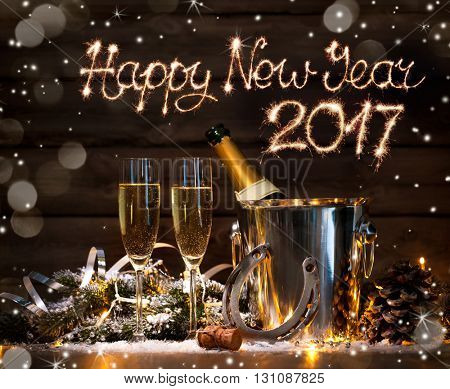 New Years Eve celebration background with pair of flutes and bottle of champagne in  bucket  and a horseshoe as lucky charm poster