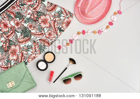fashion urban summer outfit, girl clothes set, cosmetics, makeup accessories. stylish handbag clutch, trendy pink dress, necklace hat, sunglasses. woman essentials. unusual overhead, top view on gray