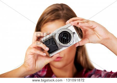 Young smiling woman making a photo through old photo camera