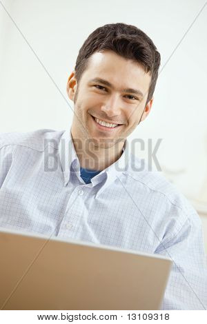 Happy young man working on laptop computer, smiling.