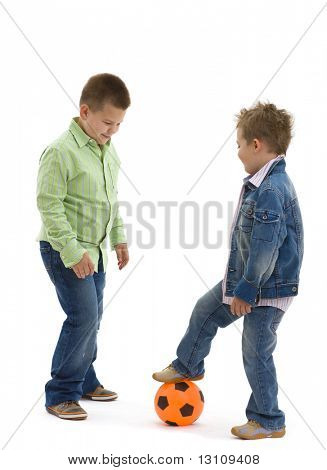 Young brothers wearing trendy jeans clothers, playing football, on isolated white background.