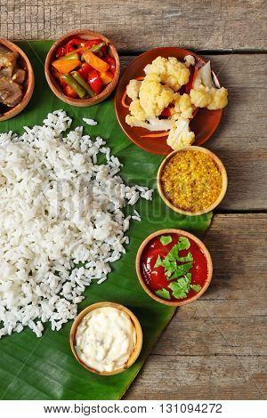 Boiled rice with vegetables and spices on banana leaf over wooden background