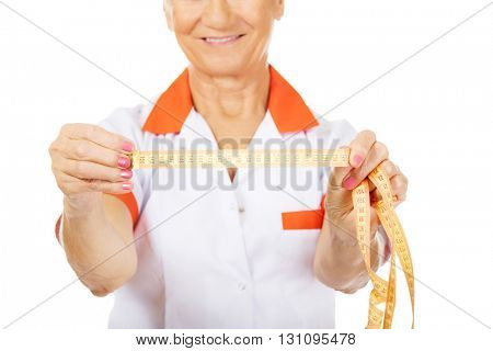 Smile elderly doctor or nurse holds measuring tape