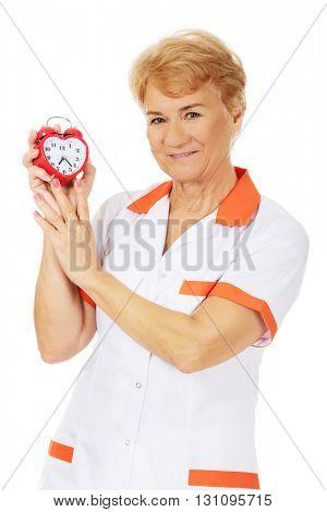 Smile elderly female doctor or nurse holds alarm clock