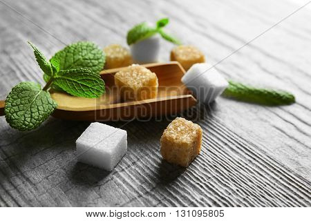 Pile of brown sugar cubes and stevia  on grey wooden background