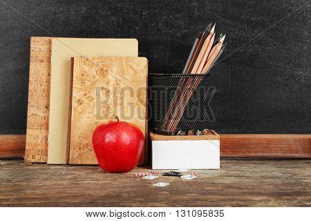 School supplies on old wooden table, near blackboard, close up