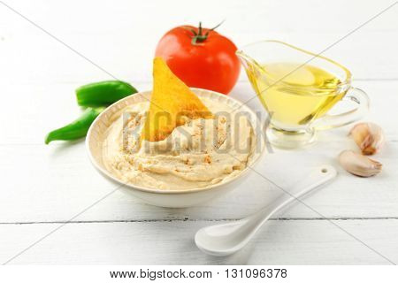 Ceramic bowl of tasty hummus with chips, oil and vegetables on table