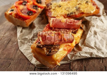 Hot pizza baguette with bacon and cheese on wooden table
