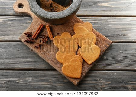 Heart shaped biscuits and cinnamon on cutting board, top view
