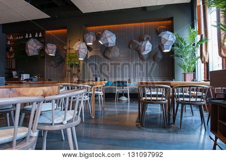 Modern design of interior in a restaurant. Elegant tables with chairs create pleasant atmosphere