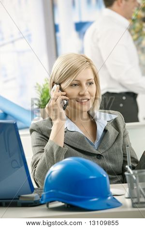 Smiling professional talking on phone in architect office.?