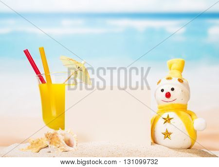 Blank card, cocktail, snowman, sea shells and a star in the sand on the seashore.