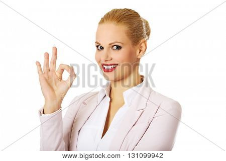 Young happy business woman shows OK sign
