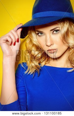 Bright fashion concept.  Beautiful girl with curly blonde hair wearing blue dress posing over yellow background.