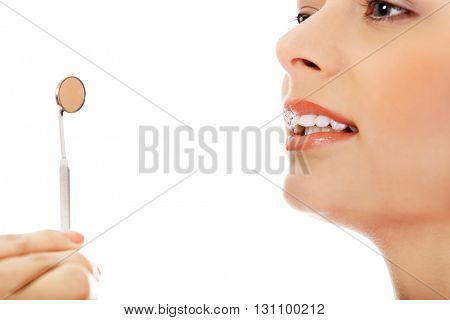 Young woman teeth and a dentist mouth mirror