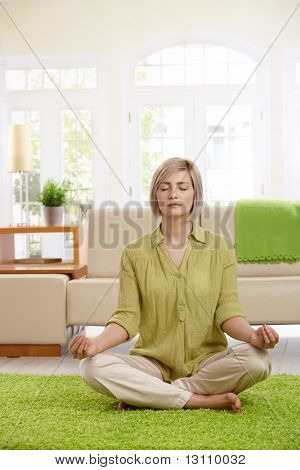Woman sitting on floor at home doing yoga meditation.?