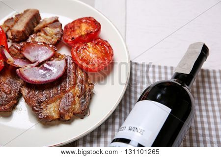Roasted beef fillet and grilled vegetables on plate, on wooden background