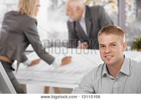 Jungen Büroangestellten im Fokus Lächeln in die Kamera, Architekt-Kollegen, die im Hintergrund arbeiten.?