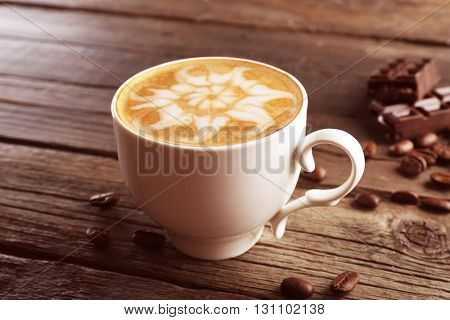Cup of coffee latte art with grains and chocolate on wooden background