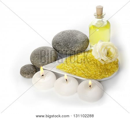 Spa still life with pebbles, oil and candles isolated on white