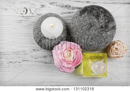 Spa still life with pebbles and oil on wooden background