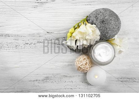 Spa still life with pebbles and cream on wooden table, top view