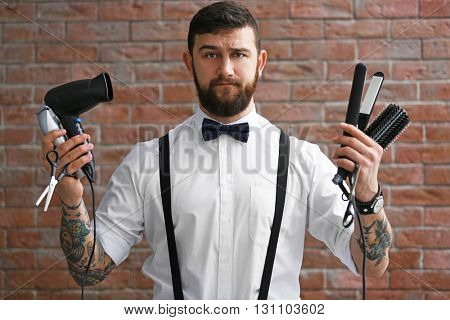 Professional hairdresser with accessories on brick wall background