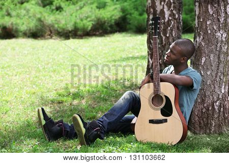 Handsome African American man with guitar sitting in park