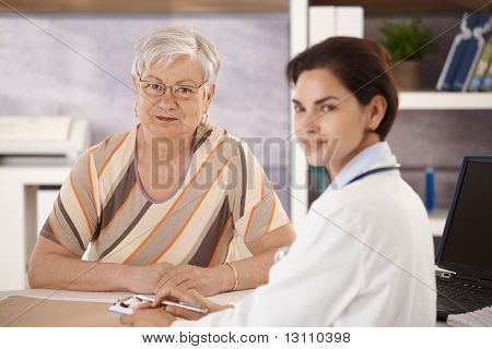Female pensioner at doctors office looking at camera.?