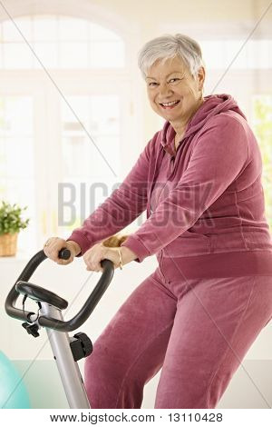 Healthy elderly woman training at home with exercise bike, smiling.?