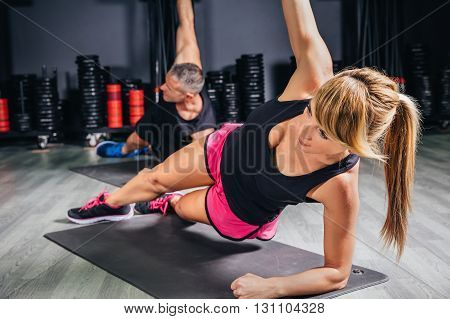 Young couple doing exercises in fitness class on sports center