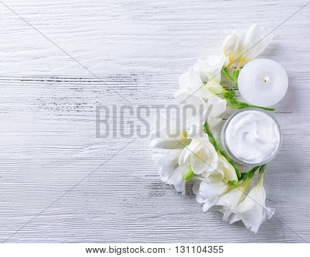 Moisturizing cream and flowers on white wooden background