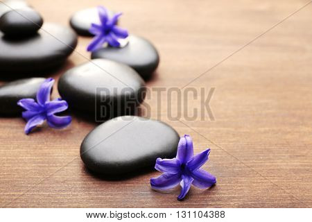 Heap of spa hot stones and flowers on wooden background