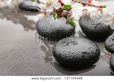 Beautiful spa composition with wet stones and flowers on grey background