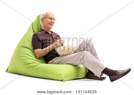 Joyful senior sitting on a green beanbag and eating popcorn isolated on white background