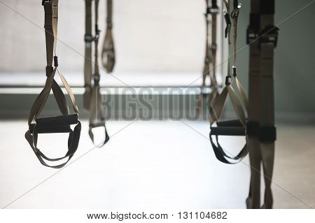 Trx equipment hanging for doing push-ups in a gym