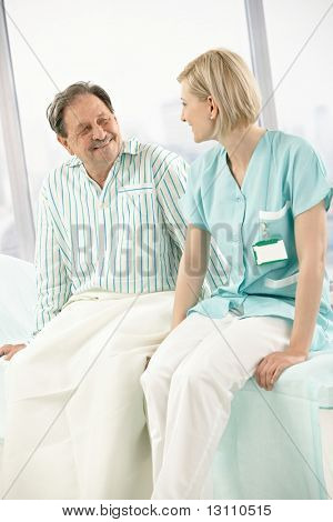 Nurse and patient sitting on hospital bed together, chatting, smiling.?