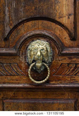 Antique knocker on a wooden door Venice Italy